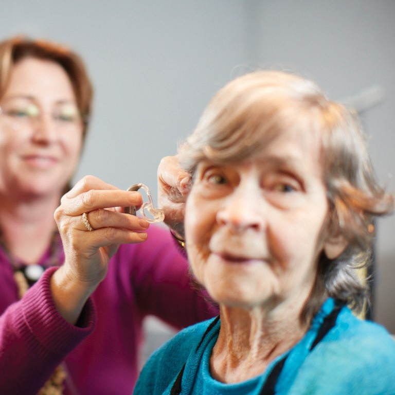 ENT Specialist fitting a hearing aid on an elderly patient